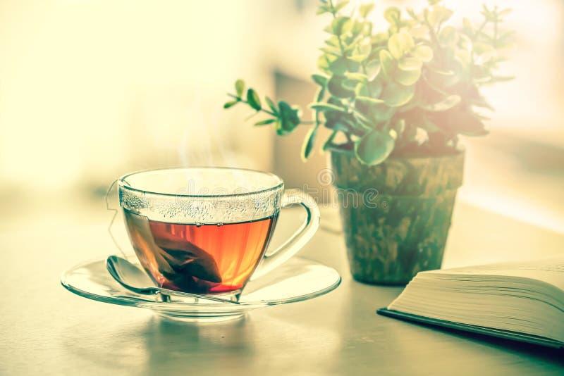 Chiuda sulla tazza di tè nero calda sulla tavola di legno in salone, con riferimento a immagini stock