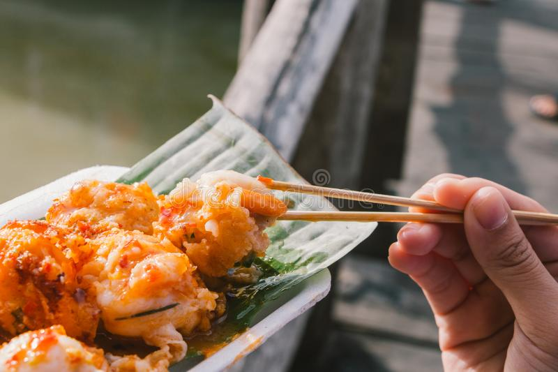 Chiuda sulla tenuta del Fried Mussels mini dai bastoncini immagini stock