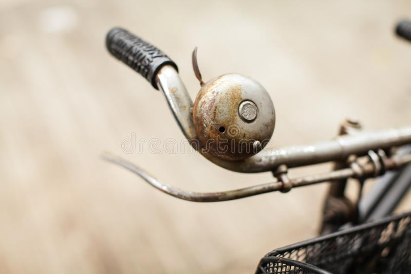 Chiuda sulla vecchia rusly campana del metallo sul manubrio di vecchia bicicletta fuori sui precedenti della via fotografia stock libera da diritti