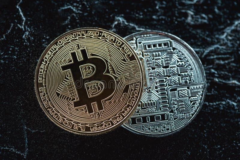chiuda sulla vista dei bitcoins dorati e d'argento sistemati su buio immagine stock