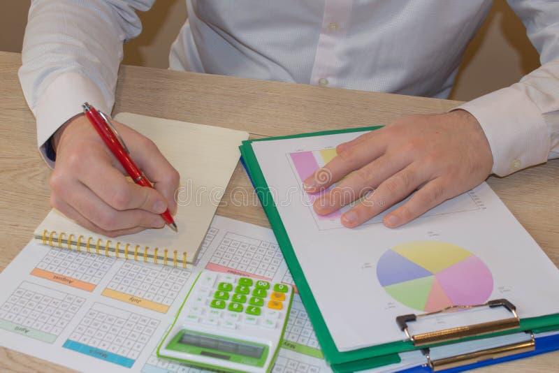 Chiuda sulla vista del contabile o delle mani finanziarie dell'ispettore che stendere il rapporto, calcolarici o controllanti l'e fotografie stock