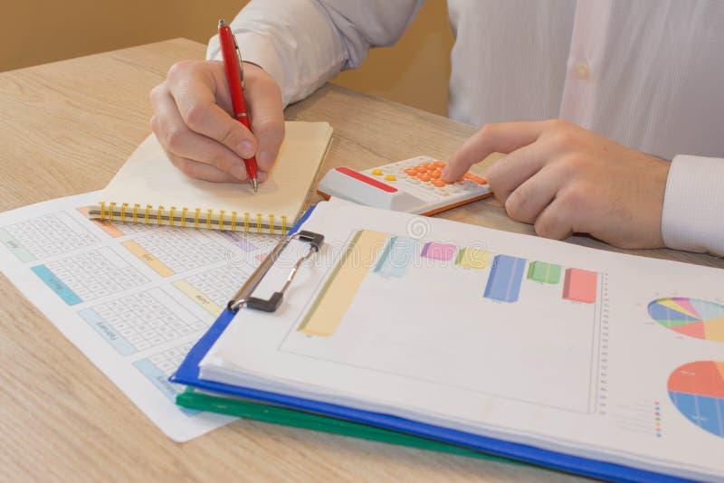 Chiuda sulla vista del contabile o delle mani finanziarie dell'ispettore che stendere il rapporto, calcolarici o controllanti l'e immagini stock