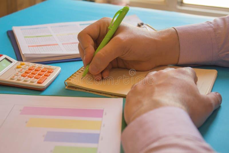 Chiuda sulla vista del contabile o delle mani finanziarie dell'ispettore che stendere il rapporto, calcolarici o controllanti l'e immagine stock libera da diritti