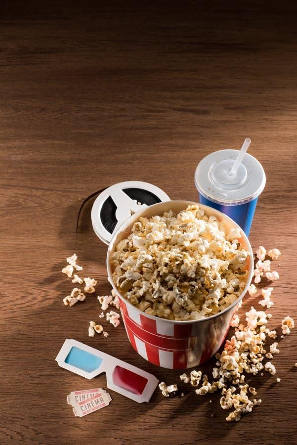 chiuda sulla vista del secchio di carta con popcorn, la bevanda della soda, i vetri 3d ed i biglietti del cinema di retor sul rip immagine stock