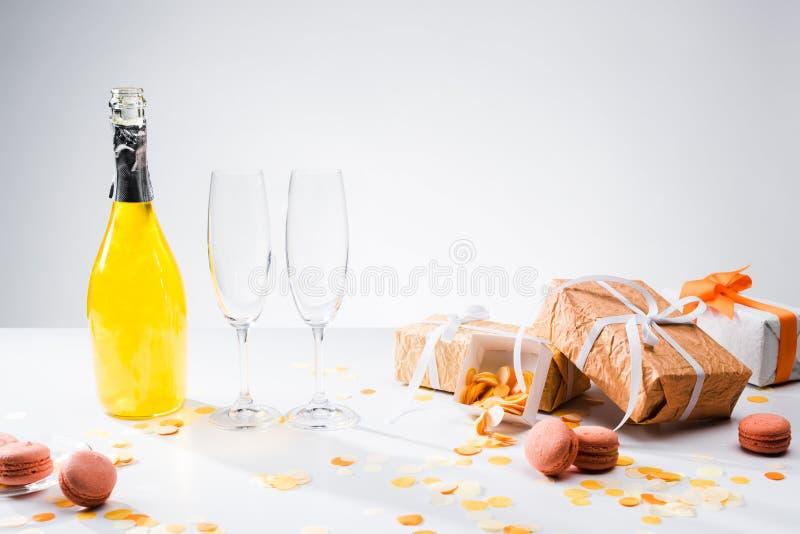 chiuda sulla vista della bottiglia di champagne giallo, di vetri vuoti, di macarons e dei regali sistemati immagine stock