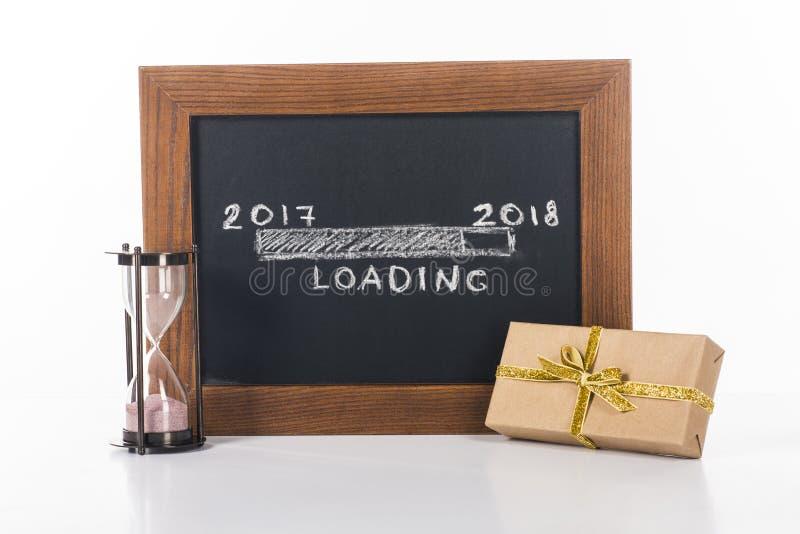 chiuda sulla vista della lavagna con 2017 - 2018 iscrizioni di carico con la clessidra ed il regalo vicino vicino fotografia stock libera da diritti