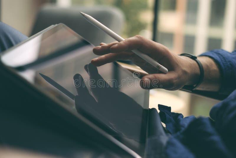 Chiuda sulla vista della mano dell'uomo d'affari facendo uso della penna dello stilo per il contatto dello schermo digitale della fotografia stock libera da diritti