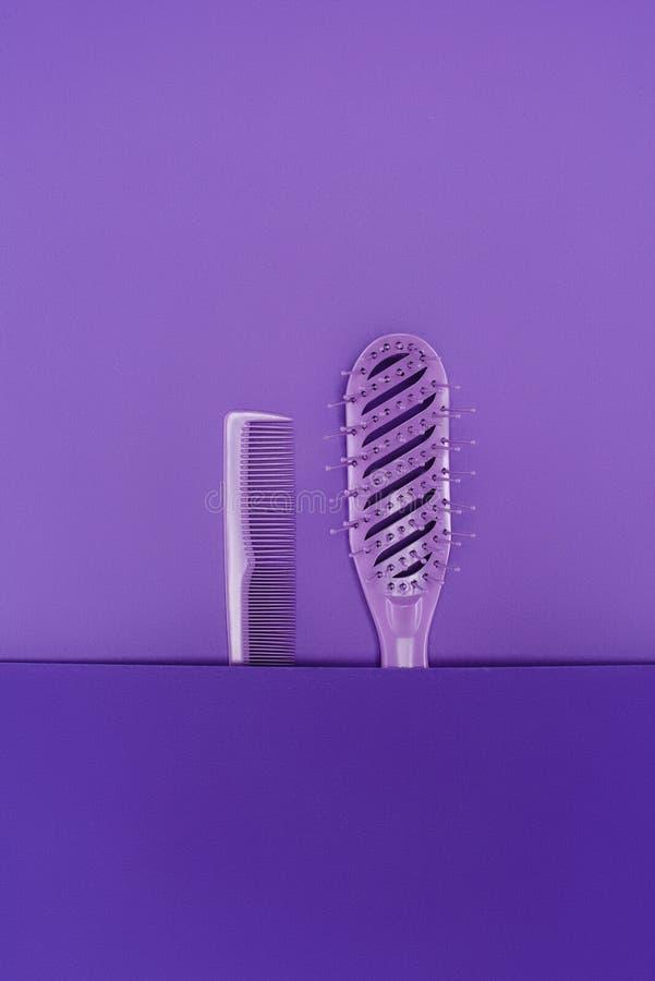 chiuda sulla vista della spazzola per i capelli porpora e pettini immagini stock libere da diritti