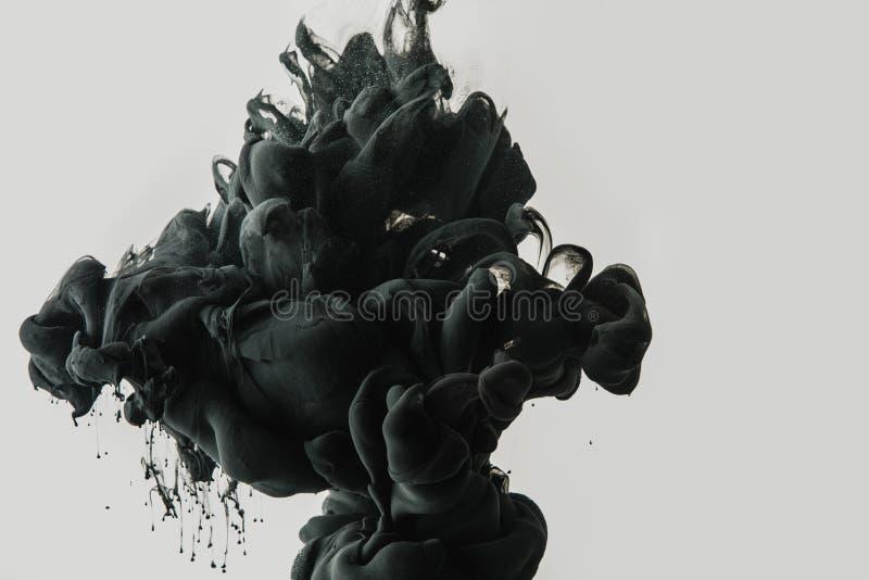 Chiuda sulla vista della spruzzata nera della pittura in acqua isolata su gray fotografie stock