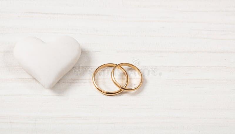 Chiuda sulla vista delle fedi nuziali dorate e di un cuore bianco, isolata, spazio della copia, su un fondo di legno bianco immagine stock