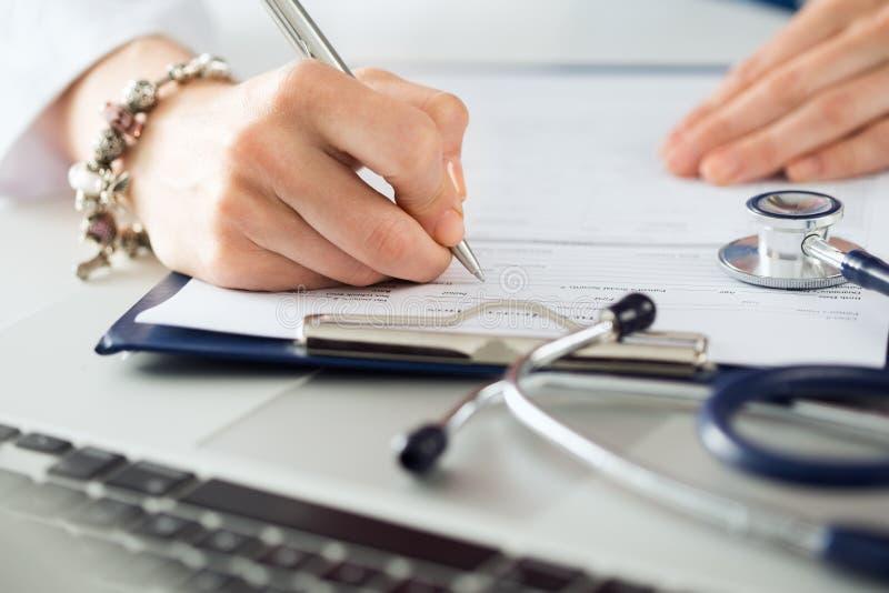Chiuda sulla vista delle mani femminili di medici della medicina che riempiono il paziente m. fotografia stock libera da diritti