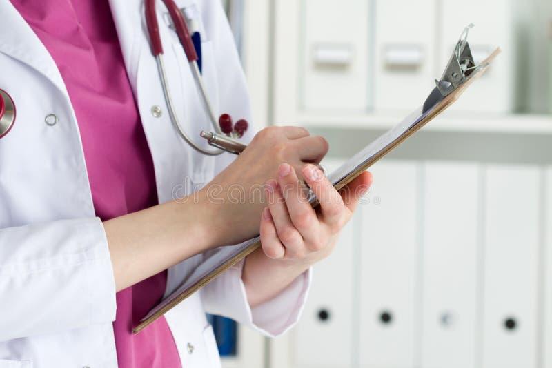 Chiuda sulla vista delle mani femminili di medico che tengono il cuscinetto del ritaglio fotografia stock libera da diritti