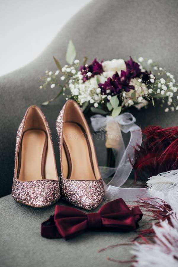 chiuda sulla vista delle scarpe, degli sposi farfallino, del mazzo di nozze e delle piume nuziali per nozze rustiche fotografie stock