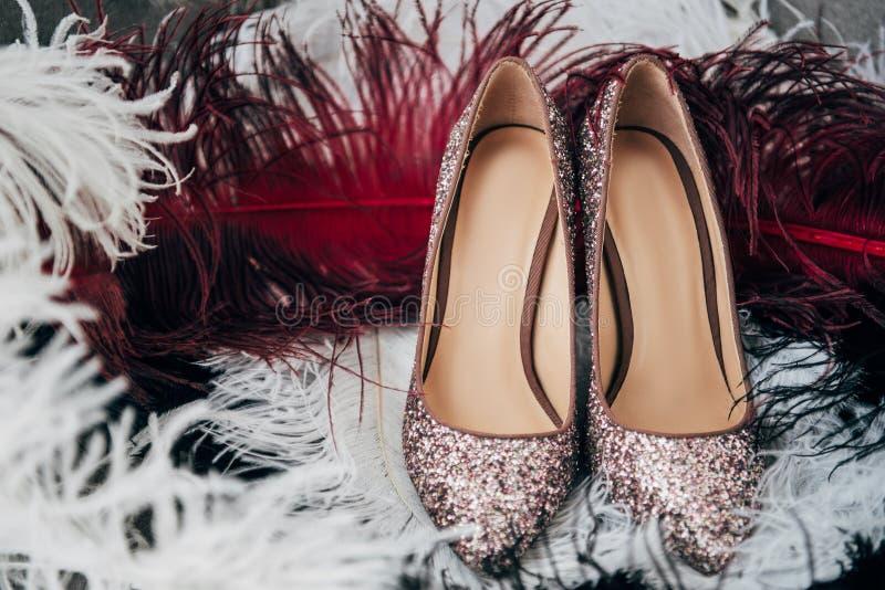 chiuda sulla vista delle scarpe nuziali e delle piume decorative fotografia stock