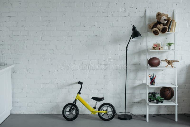chiuda sulla vista di stanza puerile vuota con la bici dell'equilibrio immagine stock libera da diritti