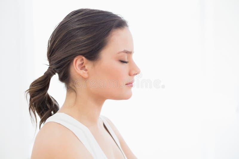 Chiuda sulla vista laterale di una giovane donna di misura con gli occhi chiusi fotografia stock