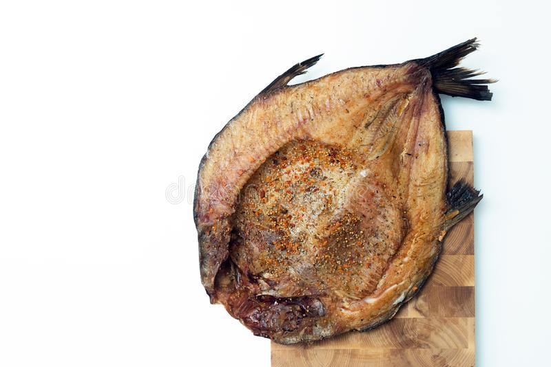 Chiuda sulla vista orizzontale dei filetti di pesce affumicati con condimento sul bordo servente di legno e sul fondo bianco immagine stock libera da diritti