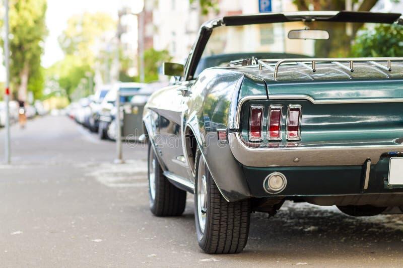 Chiuda sulla vista posteriore di vecchia automobile d'annata nera parcheggiata su una via i immagine stock libera da diritti
