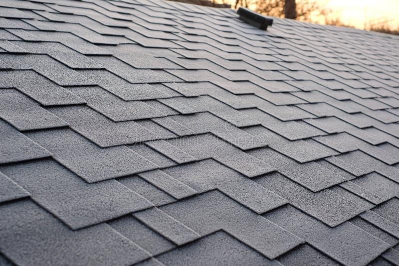 Chiuda sulla vista su Asphalt Roofing Shingles Background Assicelle del tetto - tetto Danno del tetto delle assicelle coperto di  fotografia stock