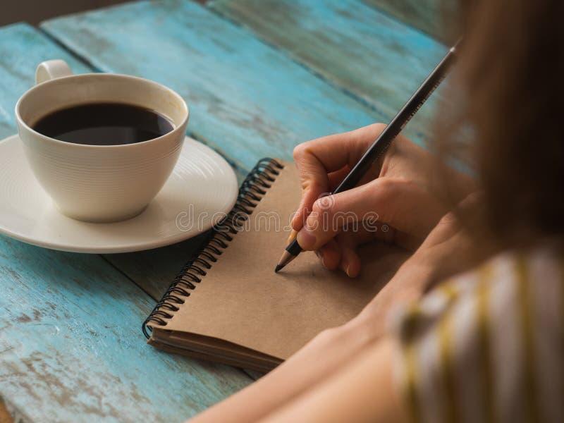 Chiuda sulla vista superiore del caffè bevente della donna di scrittura fotografie stock libere da diritti