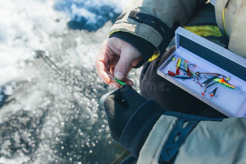 Chiuda sulle attrezzature e sulle attrezzature di pesca sul ghiaccio concetto di vacanze invernali e della gente immagine stock