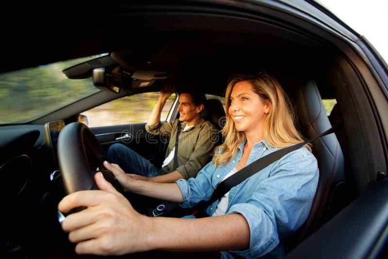 Chiuda sulle coppie felici che sorridono in automobile sul viaggio stradale fotografie stock