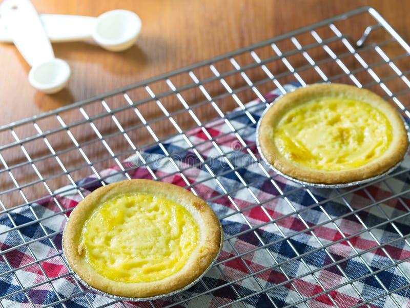 Chiuda sulle crostate dell'uovo sullo scaffale di raffreddamento Priorità bassa di legno Le crostate portoghesi dell'uovo, è un g fotografia stock