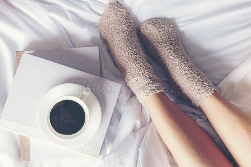 Chiuda sulle donne delle gambe sul letto bianco Il libro di lettura delle donne ed il caffè bevente nella mattina si rilassano l' immagini stock