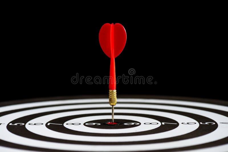 Chiuda sulle frecce dei dardi di rosso del colpo nel centro dell'obiettivo fotografia stock