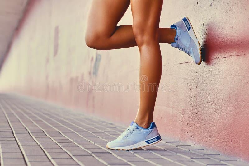 Chiuda sulle gambe del ` s della donna di abbronzature immagine stock