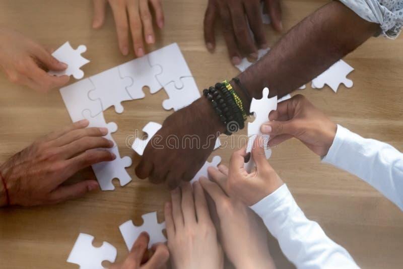 Chiuda sulle mani da sopra del puzzle di montaggio della diversa gente immagini stock