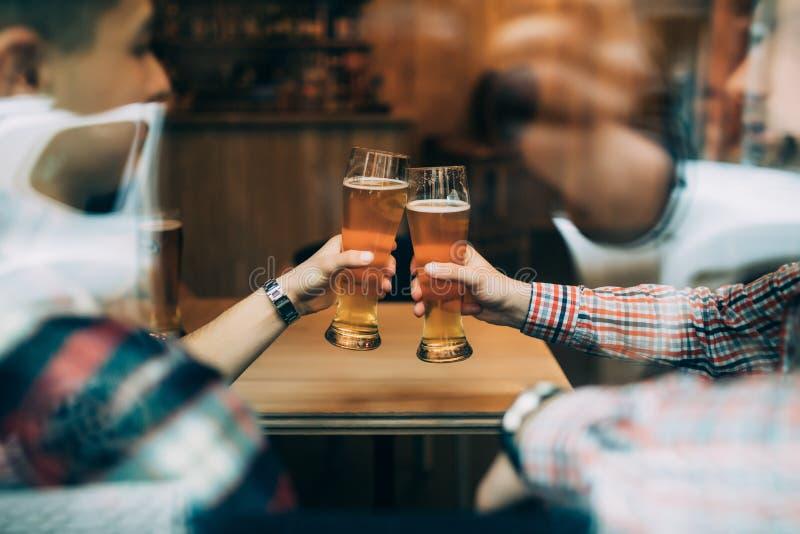 Chiuda sulle mani degli amici che si siedono all'acclamazioni del pub con la finestra della depressione di vetro di birre immagine stock libera da diritti