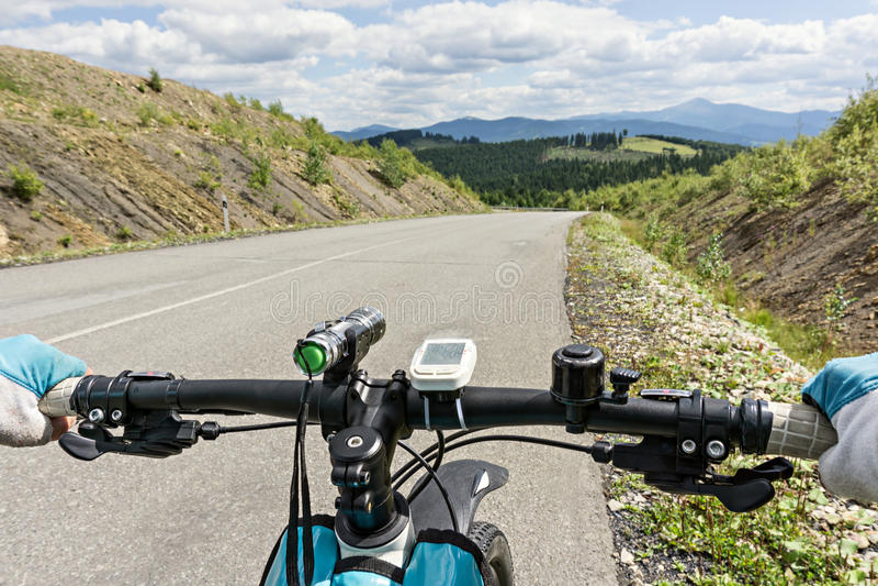 Chiuda sulle mani dei cavalieri della bicicletta su un manubrio della bicicletta fotografia stock libera da diritti