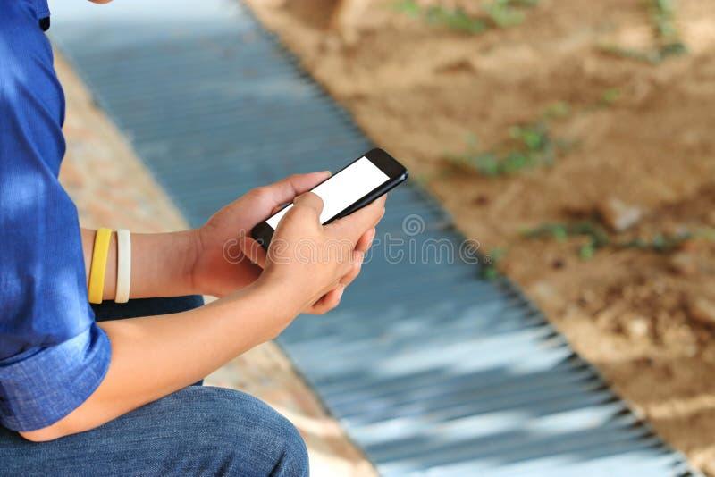 Chiuda sulle mani dell'adolescente che per mezzo dello Smart Phone mobile Il sociale trascura il concetto di crisi fotografia stock