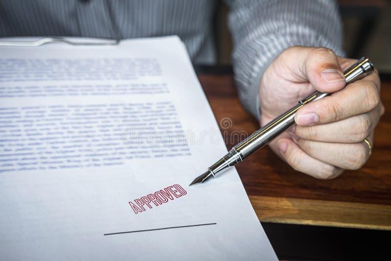 Chiuda sulle mani dell'uomo d'affari che indicano la firma ed il bollo sul documento cartaceo per approvare l'accordo di contratt fotografia stock