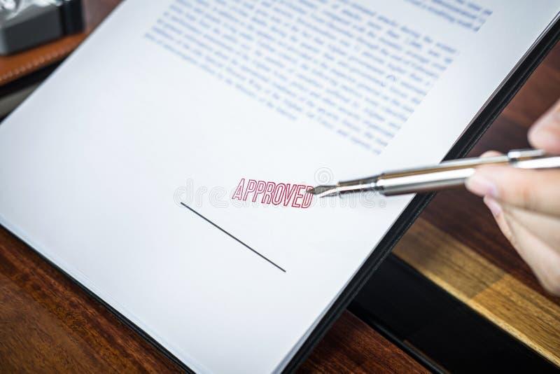 Chiuda sulle mani dell'uomo d'affari che indicano la firma ed il bollo sul documento cartaceo per approvare l'accordo di contratt fotografie stock libere da diritti