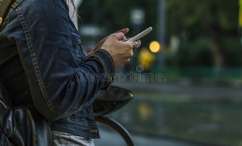 Chiuda sulle mani della donna facendo uso del telefono cellulare in città un giorno piovoso fotografia stock