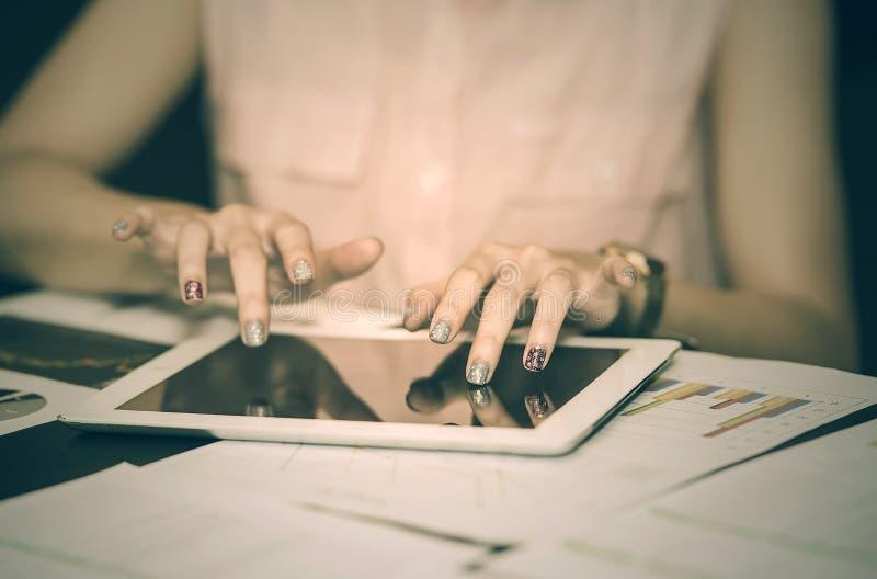 Chiuda sulle mani della donna usando e toccando sullo schermo della compressa immagine stock libera da diritti