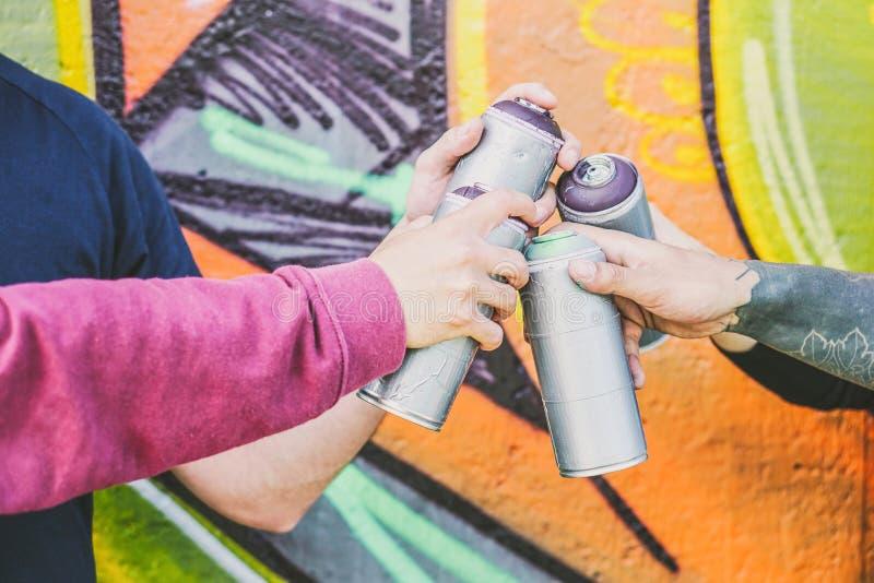 Chiuda sulle mani della gente che tiene le latte di spruzzo di colore contro la parete dei graffiti - artisti dei graffiti sul la immagini stock libere da diritti