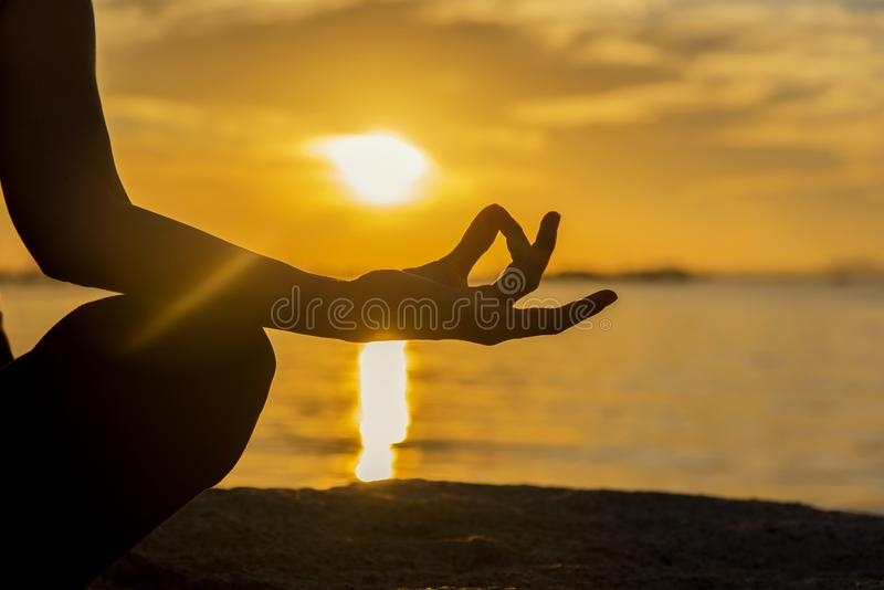 Chiuda sulle mani della siluetta La donna fa l'yoga all'aperto Esercitazione della donna vitale e meditazione per il club di stil immagini stock libere da diritti