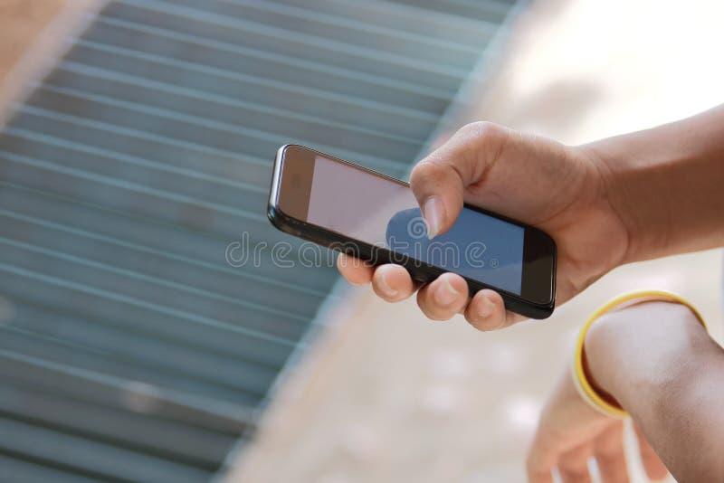 Chiuda sulle mani di adolescente facendo uso dello Smart Phone mobile su fondo vago fotografie stock libere da diritti