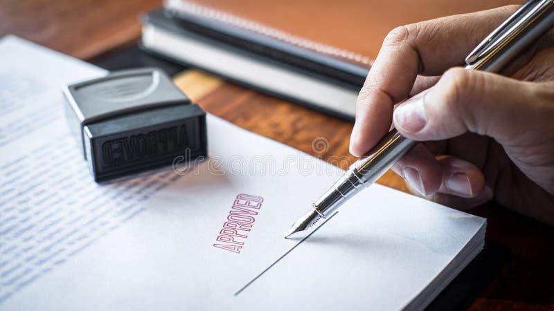 Chiuda sulle mani di firma e del bollo dell'uomo d'affari sul documento cartaceo per approvare l'accordo di contratto di investim fotografie stock