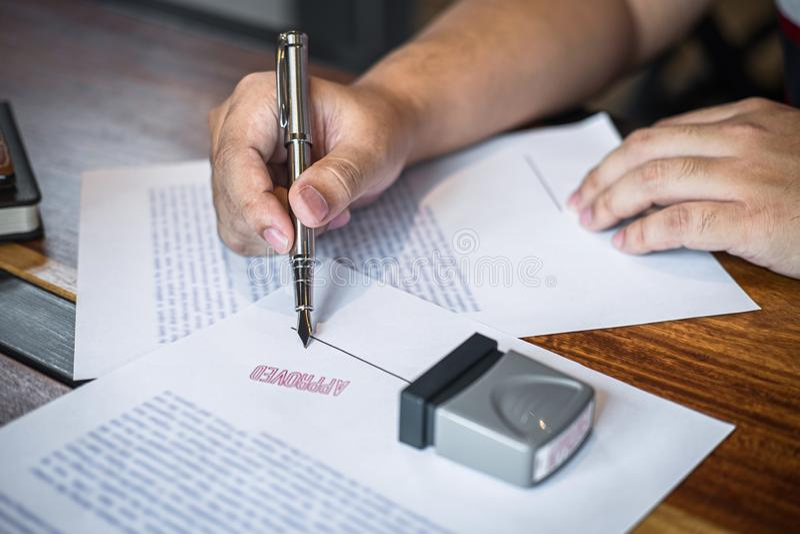 Chiuda sulle mani di firma e del bollo dell'uomo d'affari sul documento cartaceo per approvare l'accordo di contratto di investim fotografia stock libera da diritti