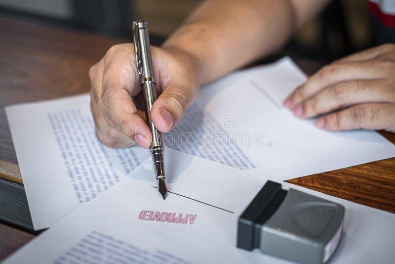 Chiuda sulle mani di firma e del bollo dell'uomo d'affari sul documento cartaceo per approvare l'accordo di contratto di investim fotografie stock libere da diritti