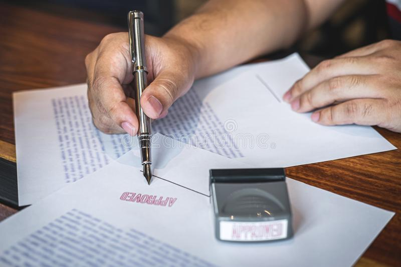 Chiuda sulle mani di firma e del bollo dell'uomo d'affari sul documento cartaceo per approvare l'accordo di contratto di investim immagini stock libere da diritti