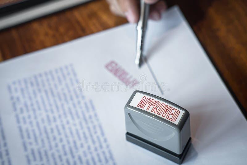 Chiuda sulle mani di firma e del bollo dell'uomo d'affari sul documento cartaceo per approvare l'accordo di contratto di investim fotografia stock