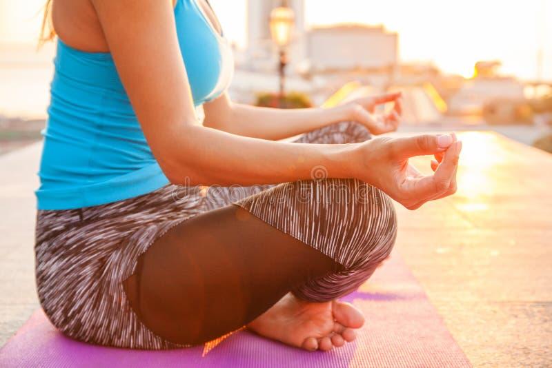 Chiuda sulle mani La donna fa l'yoga all'aperto Esercitazione della donna vitale e meditazione per il club di stile di vita di fo immagine stock