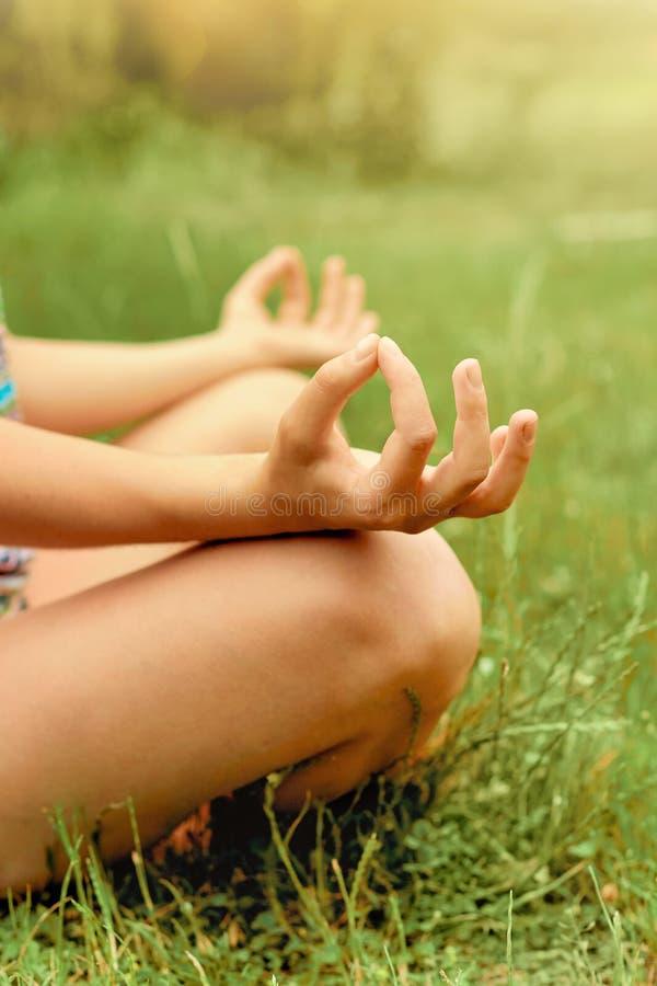 Chiuda sulle mani La donna fa l'yoga all'aperto Esercitazione della donna vitale e meditazione per il club di stile di vita di fo immagini stock libere da diritti
