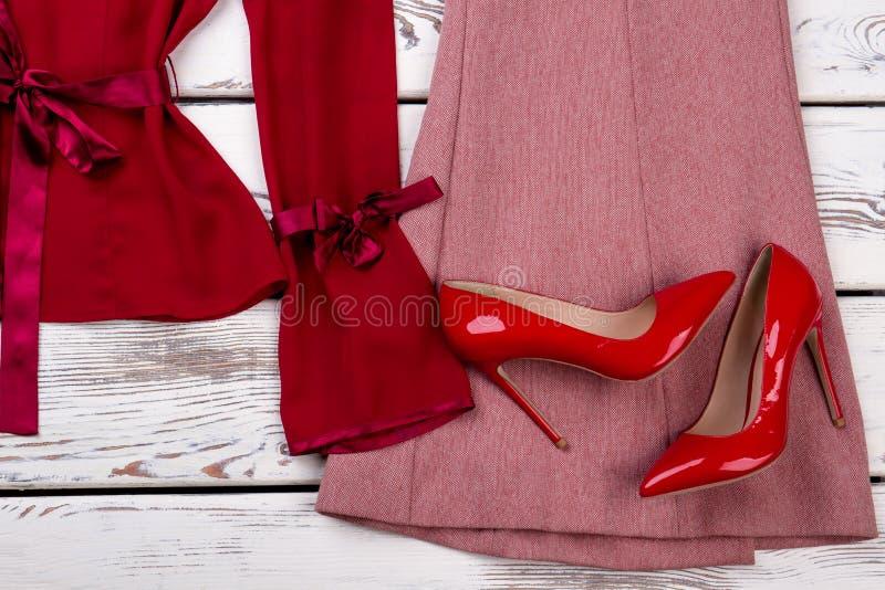 Chiuda sulle paia rosse delle scarpe del tallone sui vestiti fotografia stock