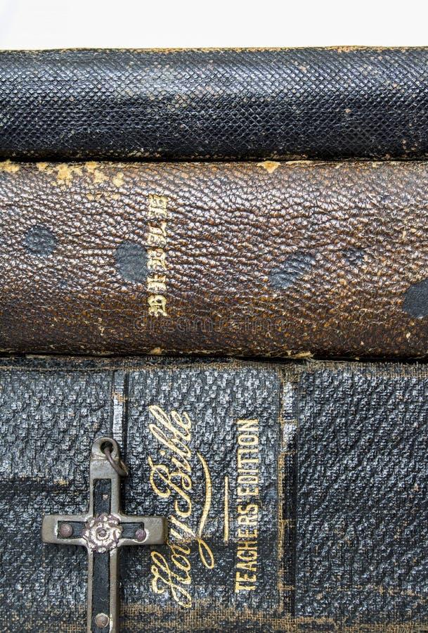 Chiuda sulle tre bibbie antiche di cuoio impilate con metallo antico fotografia stock